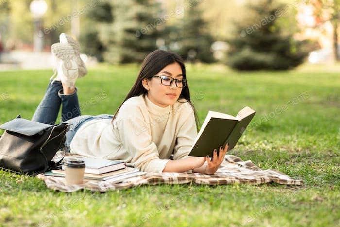 Girl reading a novel lying on the grass