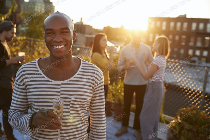Young man holding glass at a rooftop party smiling to camera