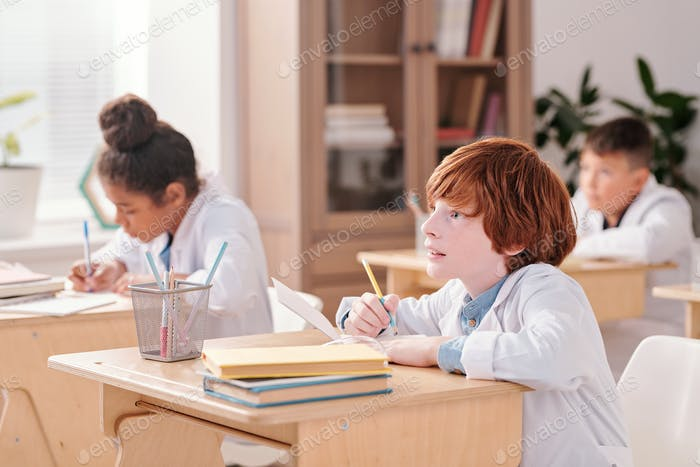 Youthful boy of elementary age in whitecoat making notes in copybook