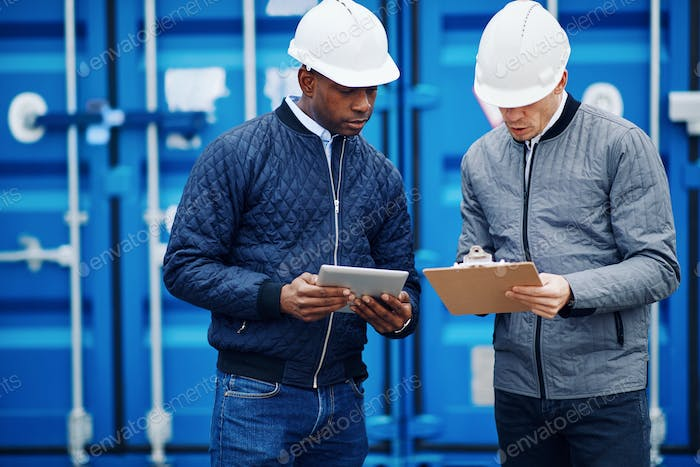 Two engineers standing in a freight yard tracking shipping containers