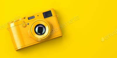 Yellow vintage photo camera on yellow background.