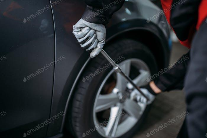 Mechanic unscrews the wheel in tire service