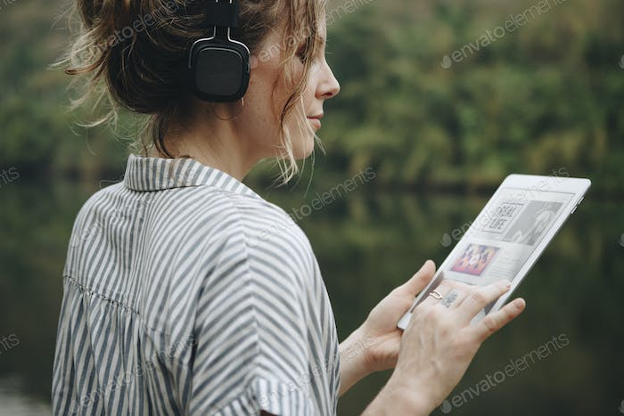 A woman alone in nature listening to music