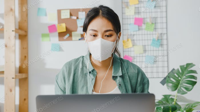 Asian woman wearing mask using laptop talk to colleagues in video call while working from home.