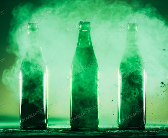 Three green bottles standing in a green dust.