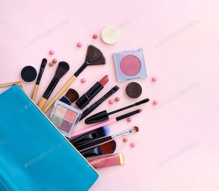 A blue cosmetics bag with makeup products spilling out on to a p