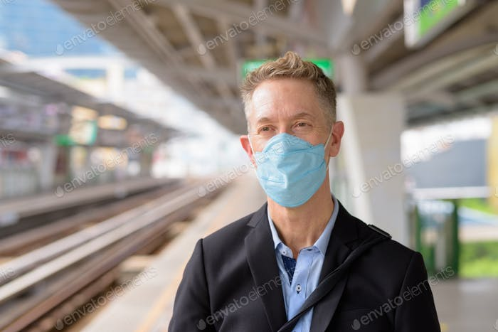 Face of mature businessman with mask thinking and waiting at the sky train station