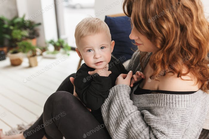 Young mother sitting on floor holding her little handsome son that dreamily looking in camera