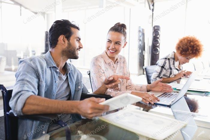 Junge Geschäftskollegen diskutieren im Kreativbüro