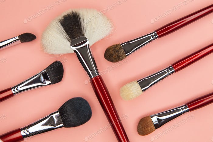 set of brushes for applying cosmetics on a pink background