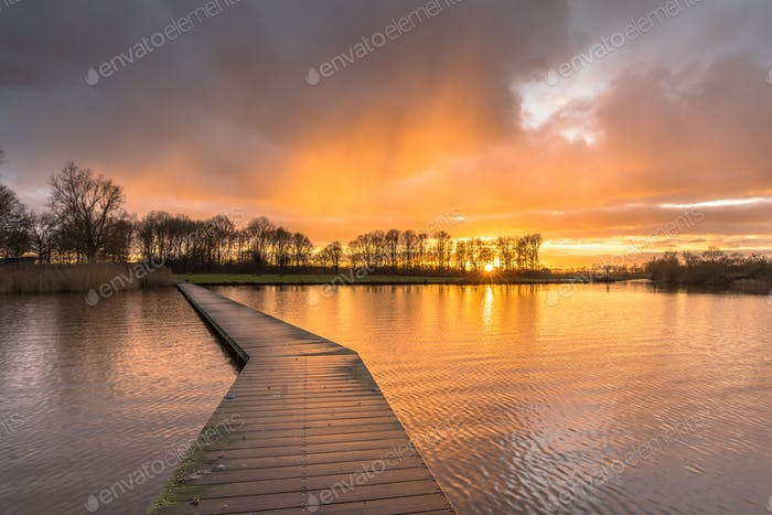 Thumbnail for Wooden walkway in lake under orange sunset