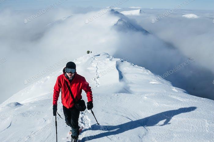 Anführer-Bergsteiger läuft vor dem Team in verschneiten Gorgany-Bergen