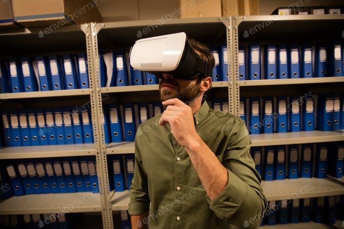 Businessman wearing VR glasses in file storage room