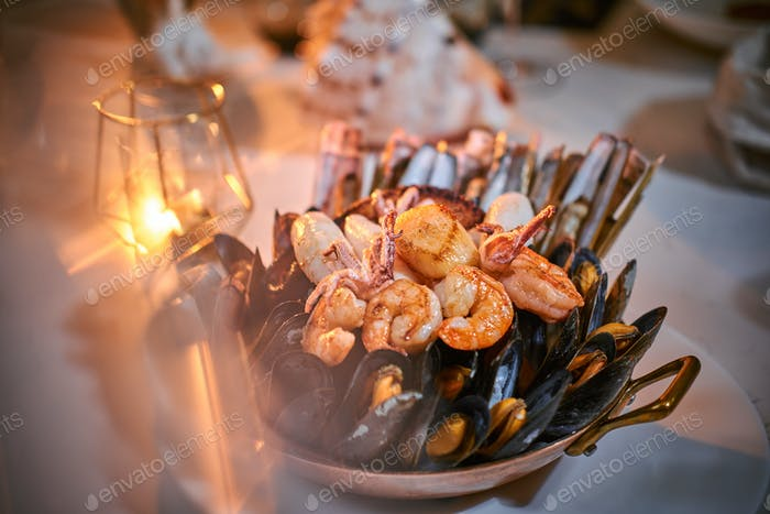 A bowl of grilled shrimps and mussels served on a stone table next to golden candle in a restaurant