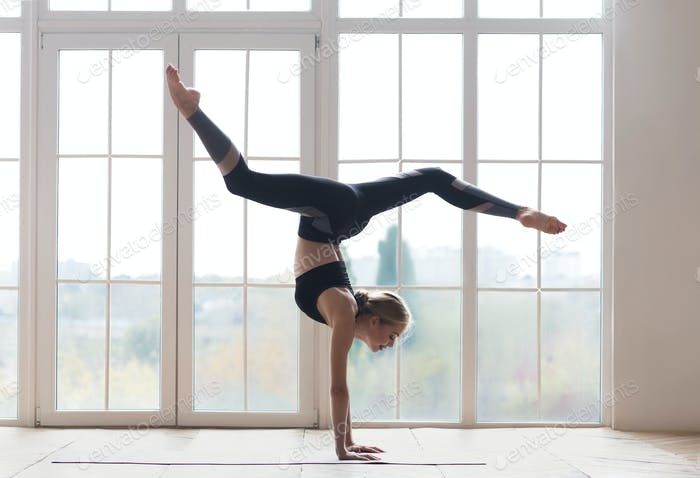 Young sporty woman balancing on hands with splitted legs