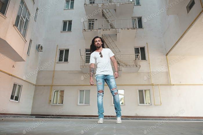 Stylish man posing on building background