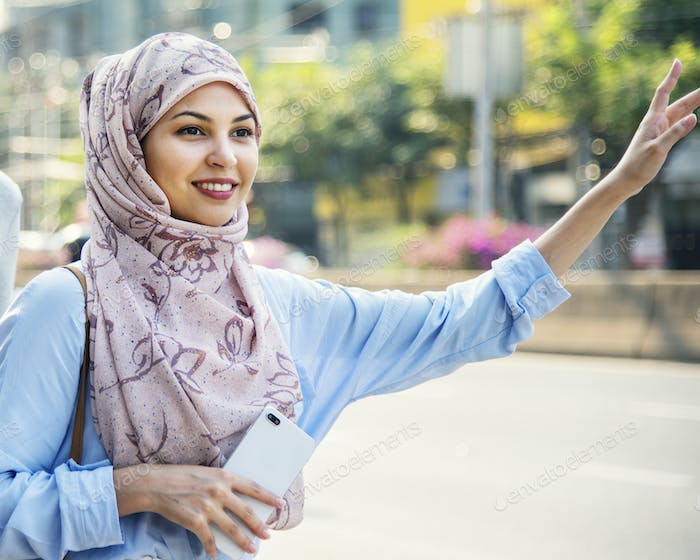 Islamic woman calling taxi in the city