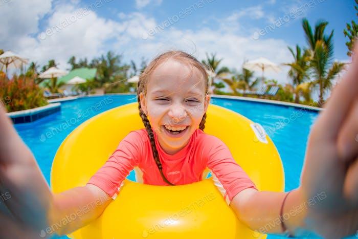Feliz niño con círculo de goma inflable divirtiéndose en la playa