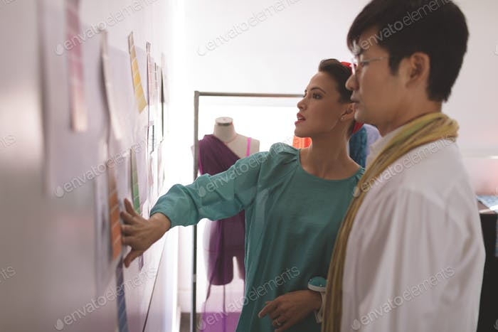 Side view of fashion Multi-ethnic designers discussing over designer sketch on wall in design studio