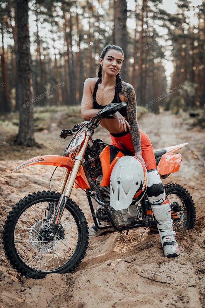Charmante junge weibliche Rennfahrerin mit halb nackten Torso sitzt auf ihrem Fahrrad im Wald