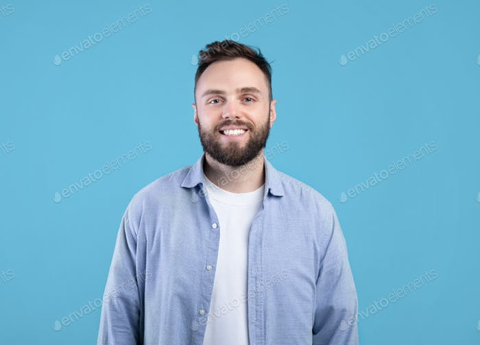 Portrait of handsome bearded young man in casual outfit smiling and looking at camera over blue