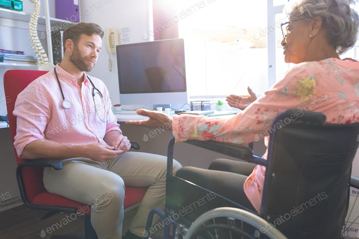 Side view of a Caucasian senior female patient talking with doctor in clinic