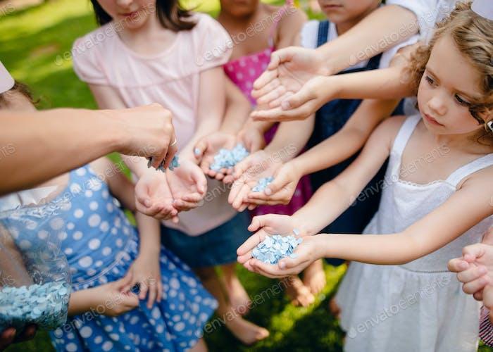 Unerkennbare kleine Kinder im Freien im Garten im Sommer, halten Konfetti