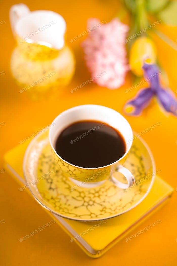 Tasse mit Kaffee, Blumen, Notizbuch auf gelbem Hintergrund