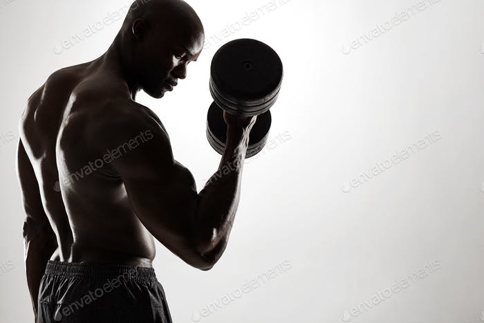 Young african man exercising with heavy dumbbells