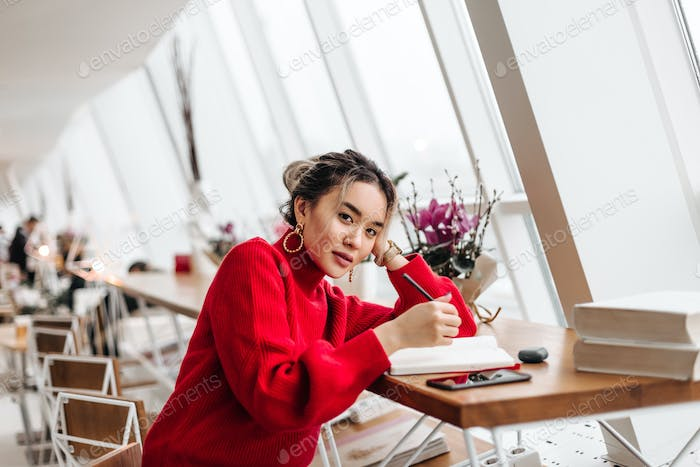 Lovely Asian girl with ponytail dressed in red oversized sweater sits in co-working space and takes