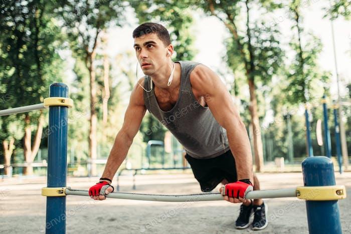 Man doing push-up exercise using horizontal bar