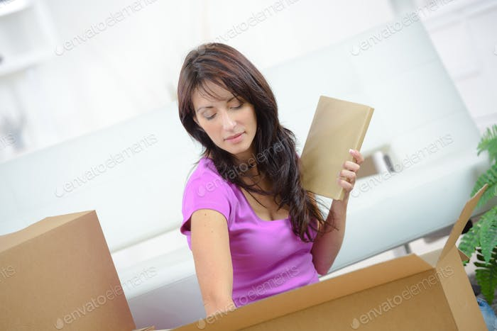Woman unpacking items from cardboard box