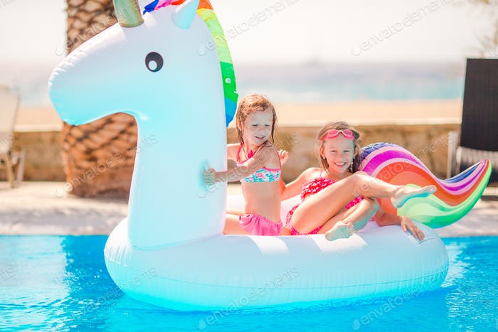 Adorable little girls at swimming pool having fun during summer vacation