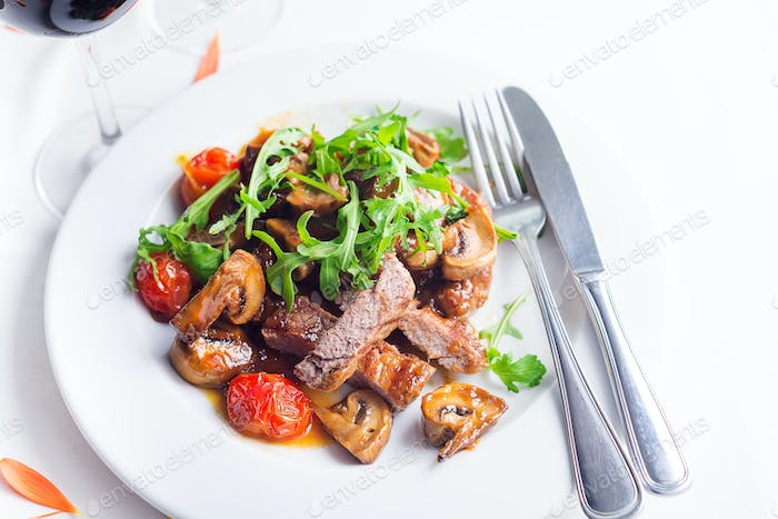 Juicy steak medium rare beef with arugula and grilled vegetables. Top view
