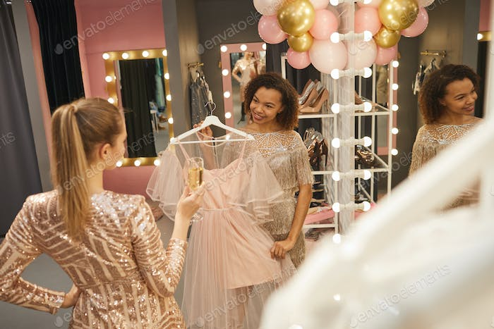 Young Women Trying on Dress in Boutique
