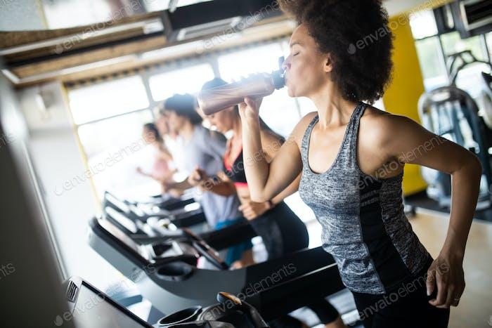Junge Frau läuft auf einem Laufband im Gesundheitsclub