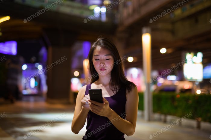 Beautiful Asian Woman Outdoors At Night Using Mobile Phone