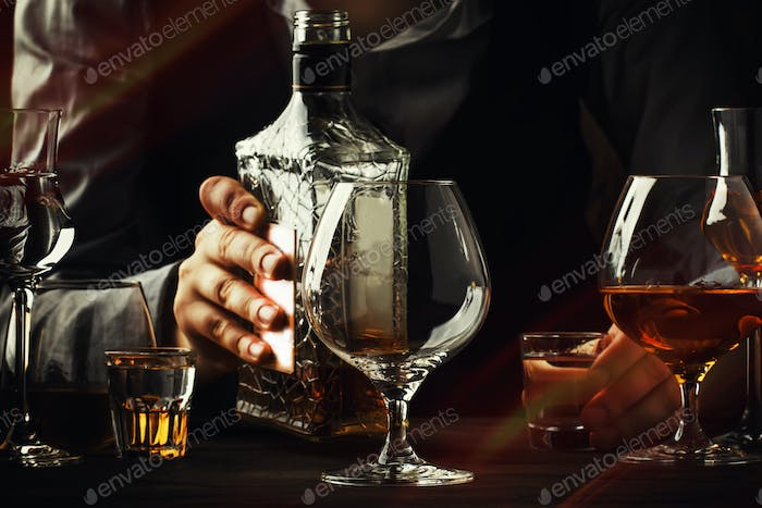 The bartender pours the cognac or brandy