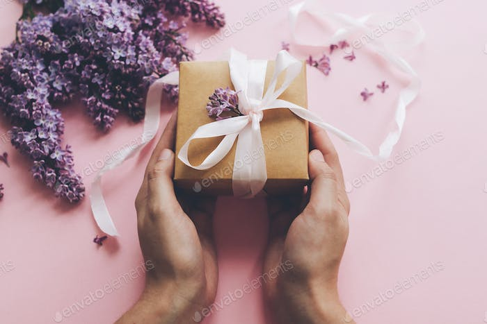 Hands holding gift box with ribbon and lilac flowers on pink background