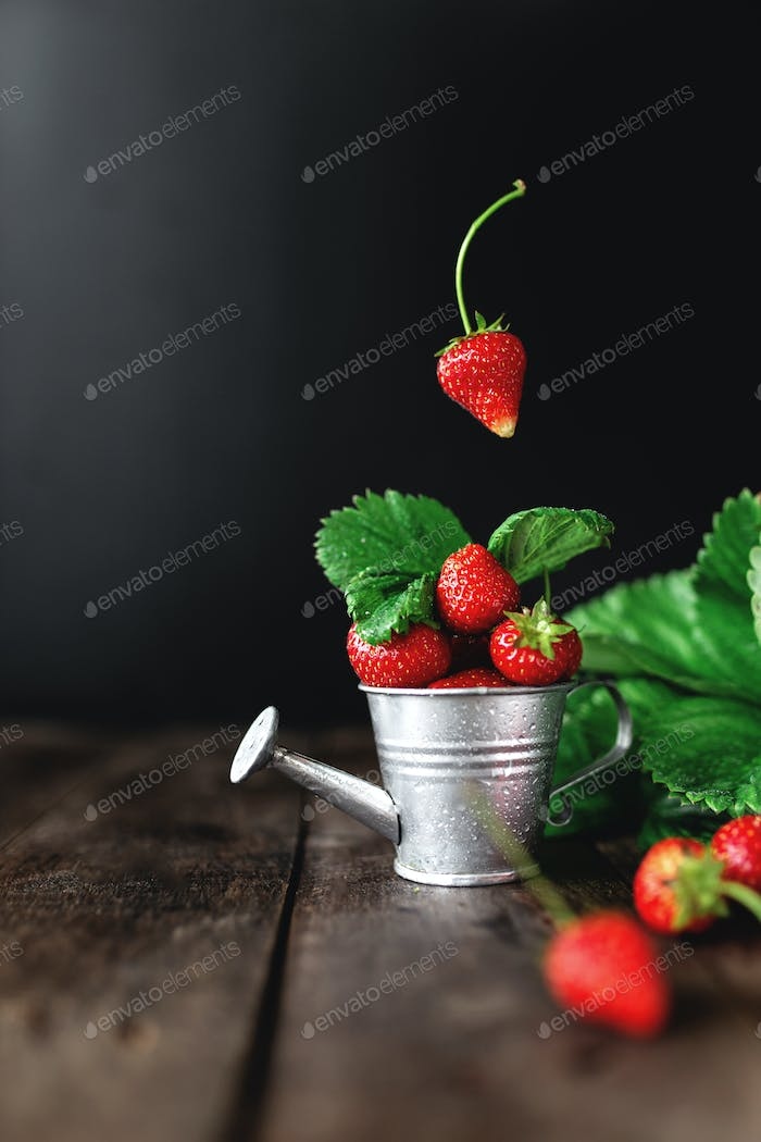 Sweet strawberries levitation on wooden background table, low key