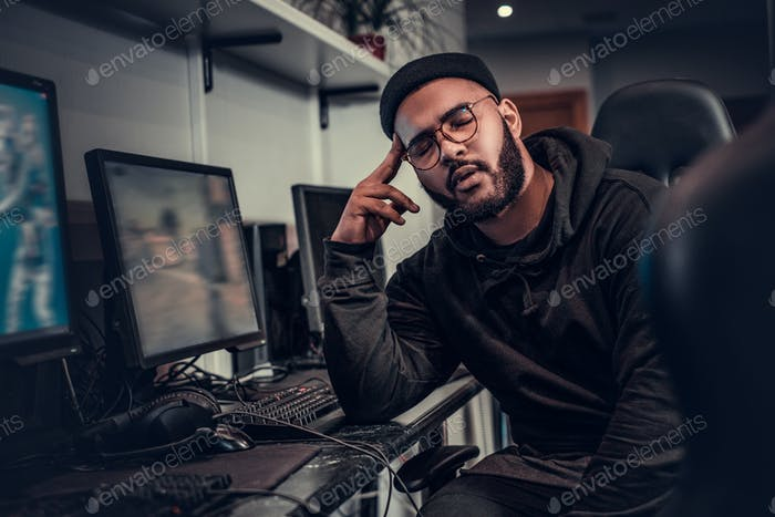 Tired African-American bearded gamer wearing hoodie