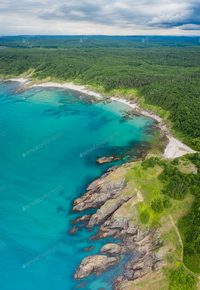 Picturesque rocky coastline with sandy beaches and green forests