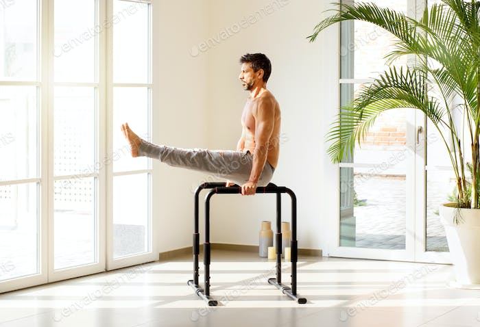Fit man doing V sit exercises on parallel bars
