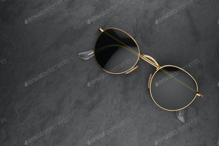Gold frame round black sunglasses on black slate background.