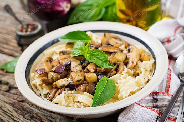 Vegetarian pasta with mushrooms and aubergines, eggplants. Italian food. Vegan meal.