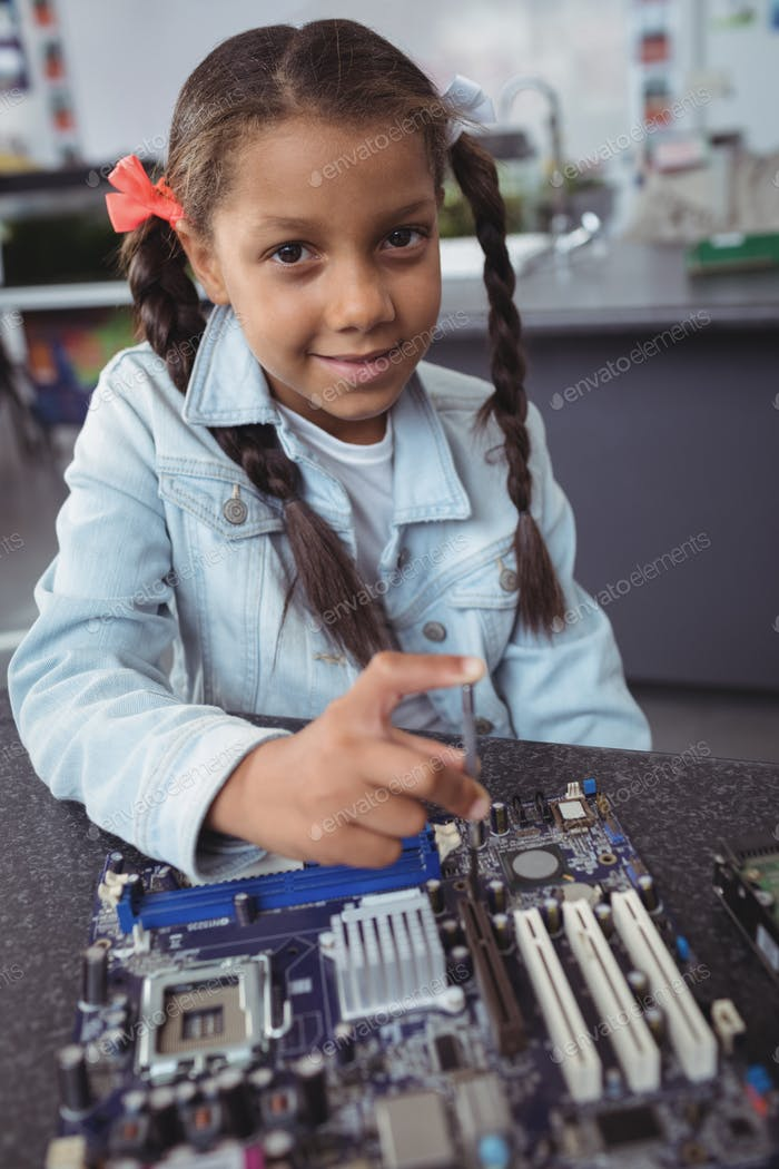 Portrait of elementary girl assembling circuit board