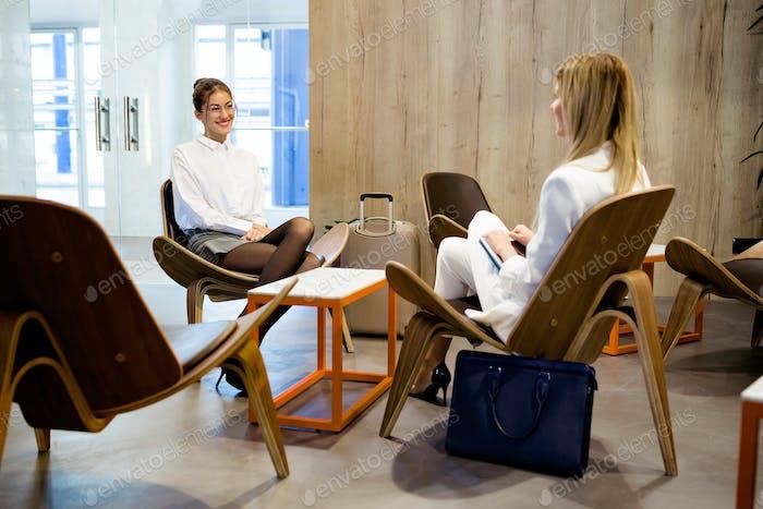 Zwei attraktive stilvolle Geschäftsfrauen sprechen über die Arbeit an der