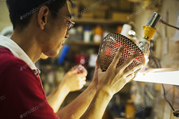 A craftsman in a glass maker's workshop holding a vase with a delicate geometric pattern up against