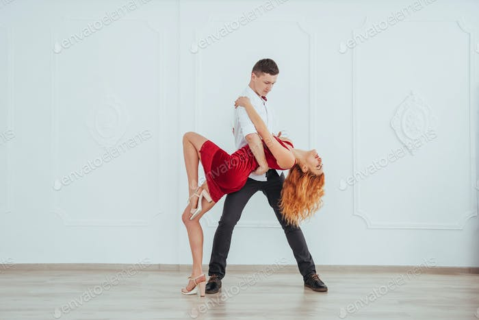 Young beautiful woman in a red dress and a man dancing, isolated on a white background.