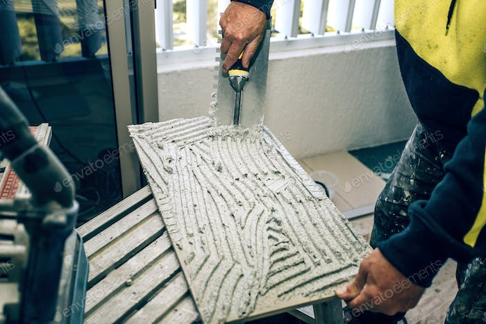 Professional builder smears cement glue on the ceramic tile with a trowel.